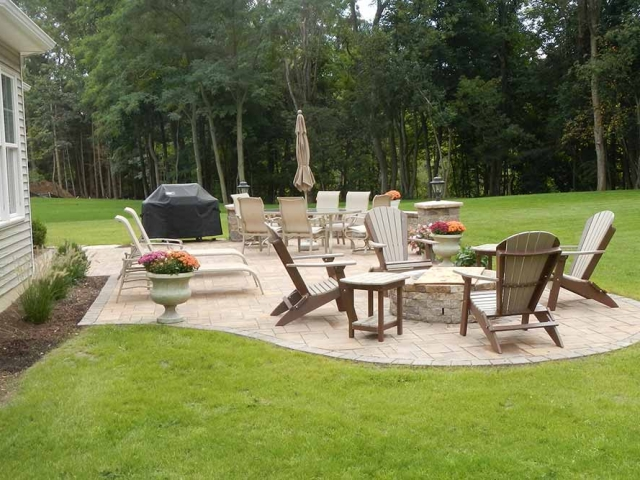 back stone patio with outdoor furniture and grass