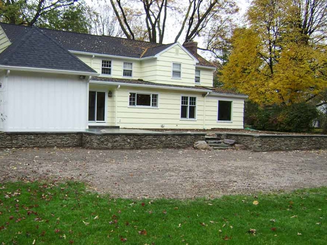 back of house with stone wall and driveway