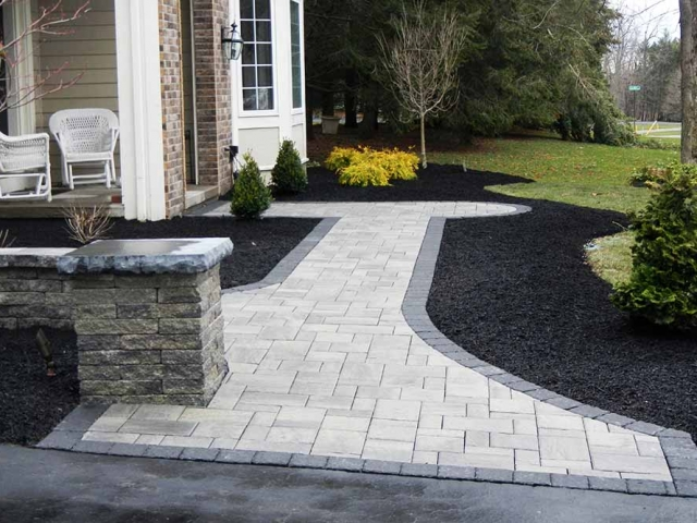 stone walkway leading to front of house with porch