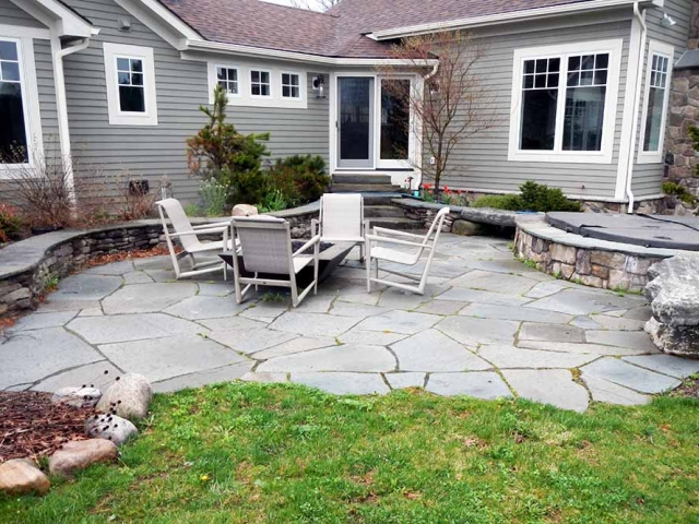 stone patio with firepit and chairs