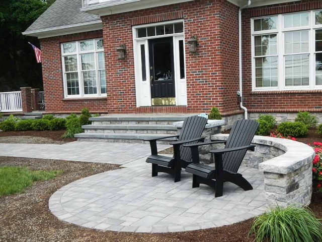 brick house with stone patio and chairs