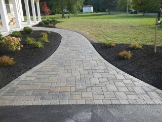 walkway of stone pavers leading to front of house with landscape and grass