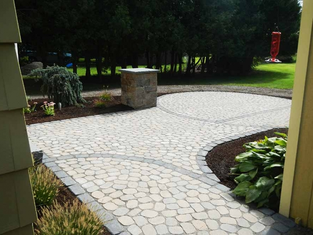 stone paver patio with hummingbird feeder and plants