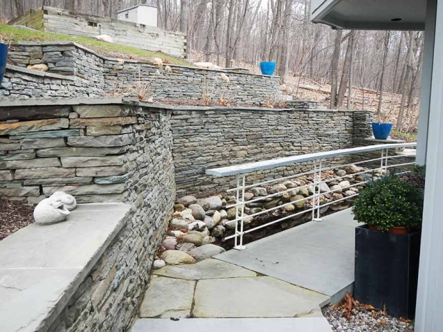 two level stone wall with sidewalk