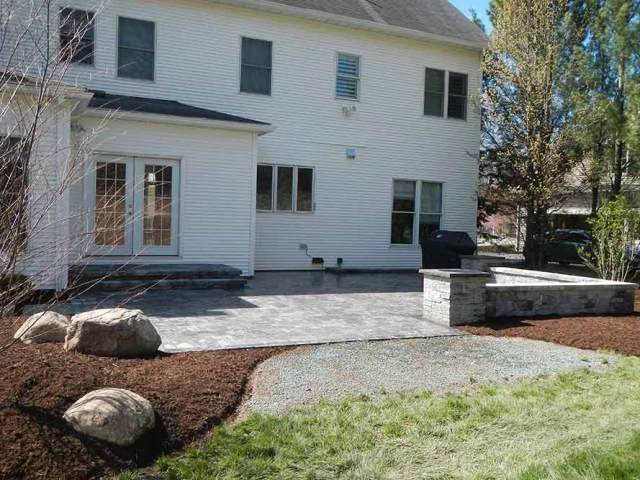 back of house with stone patio and stone wall