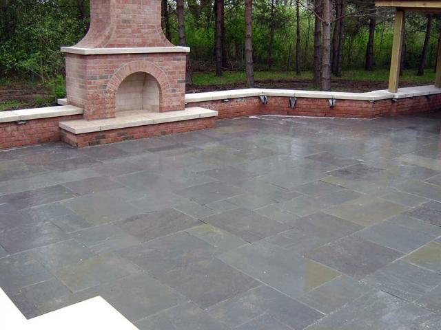 stone patio with brick fireplace in backyard