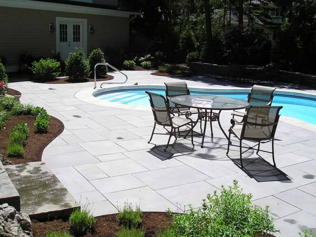 inground pool with stone deck, table and chairs and greenery