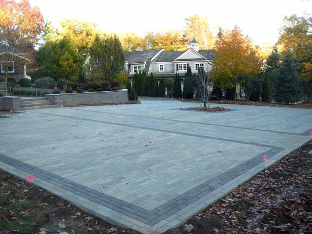 large stone patio in backyard with trees