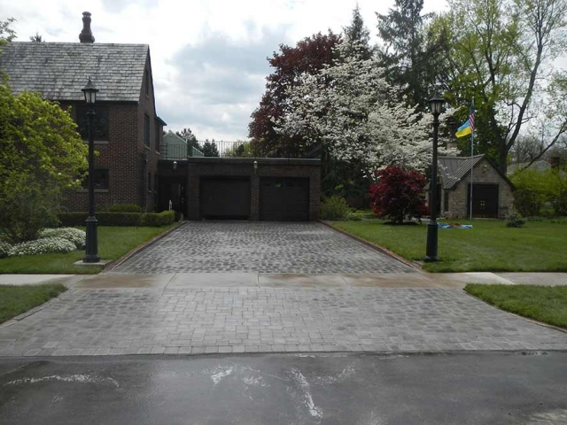 stone driveway with brick house and trees
