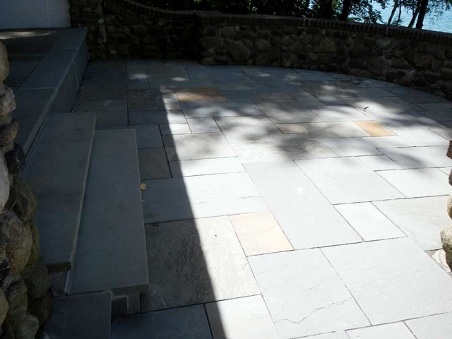stone patio area with steps and stone wall