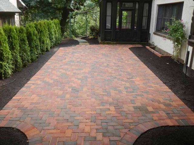 brick paver patio with trees and house