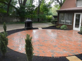 round brick patio with back door of house