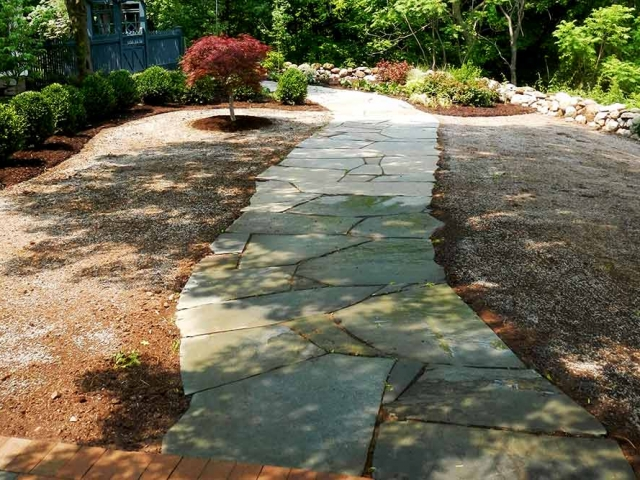 stone walkway in landscaping with bushes