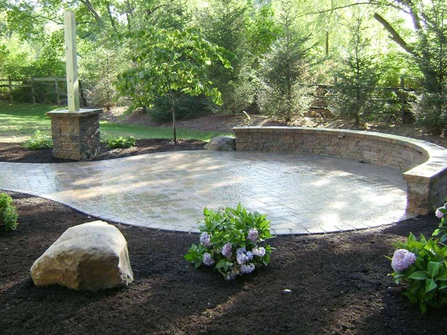 stone circular patio with stone wall and landscaping