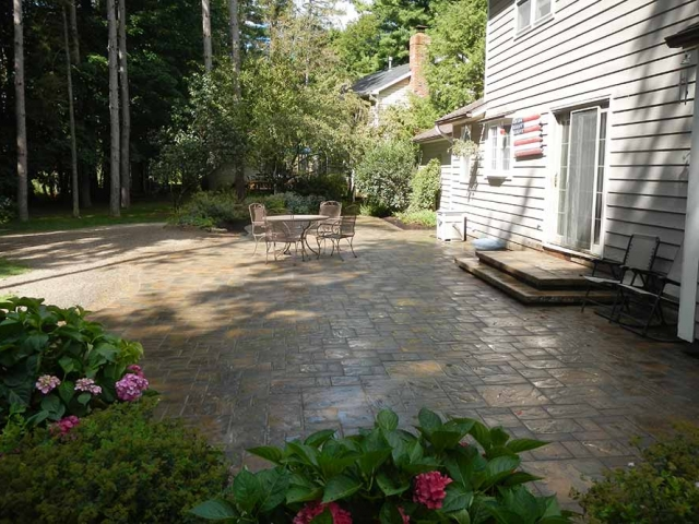 large stone patio in backyard with table and chairs
