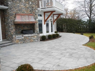 stone patio with grill and back of house